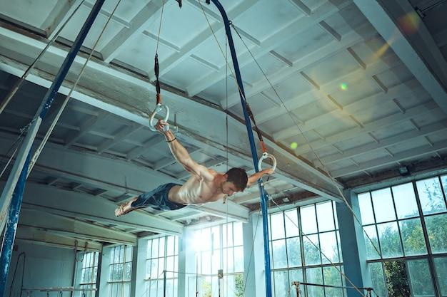 체육관에서 어려운 체조 운동을 하는 스포츠맨 스포츠 운동