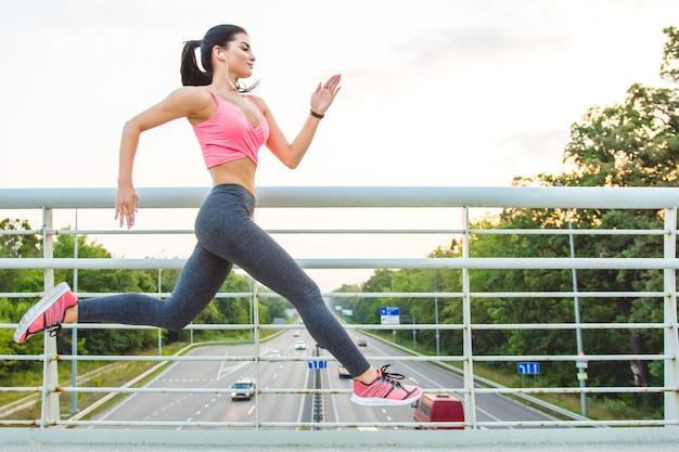 Спортсменка бежит по мосту