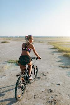 カラフルなスーツを着たスポーティな金髪の女性は、晴れた夏の日に砂漠地帯で自転車に乗ります。フィットネスのコンセプト。背面図