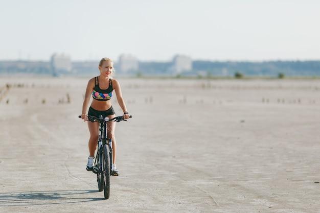 カラフルなスーツを着たスポーティな金髪の女性は、晴れた夏の日に砂漠地帯で自転車に乗ります。フィットネスのコンセプト。