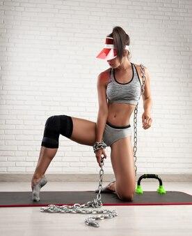 집에서 스포츠 기차를 위한 고정 무릎 패드에 스포티 한 여성이 무릎을 복원