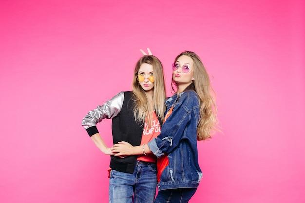 Весеннее изображение двух позитивных девушек в очках, подружек с прямыми волосами, которые обнимаются,