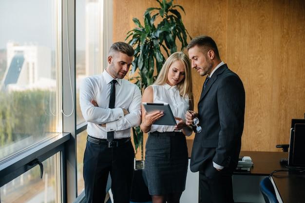 사무실 직원이 창 옆의 비즈니스 문제를 논의합니다. 비즈니스 경제학.