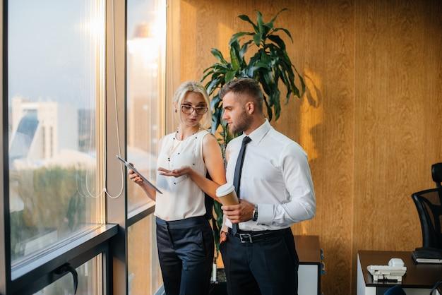 사무실 직원이 창 옆의 비즈니스 문제를 논의합니다. 비즈니스 금융.