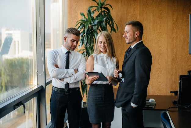 사무실 직원이 창 옆의 비즈니스 문제를 논의합니다. 비즈니스 금융