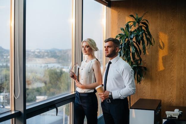 사무실의 직원이 창 옆에서 업무 문제를 논의합니다. 비즈니스 금융.