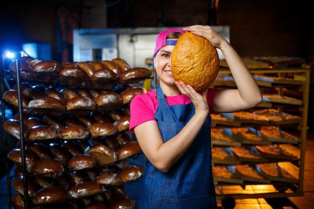 パン屋で焼く段階。パン屋の棚を背景にパンを手に持ったパン屋の女の子の肖像画。パンとパン屋の手。工業用パンの生産