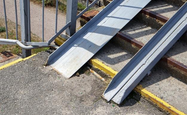 Лестница пешеходного перехода со следами разрушений. две поручни для инвалидных колясок. металлические перила для велосипедов, инвалидных колясок и колясок с детьми. спецтехника на лестнице.