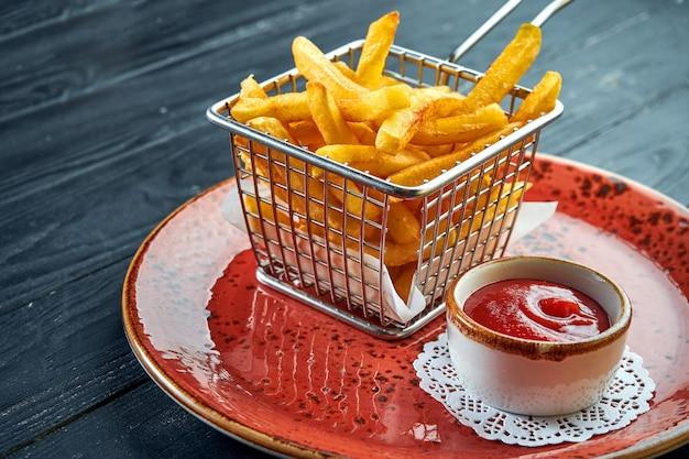 표준 반찬은 프렌치 프라이로, 붉은 소스와 함께 접시에 담긴 바구니에 담겨 제공됩니다. 검은 목재 표면. 패스트 푸드