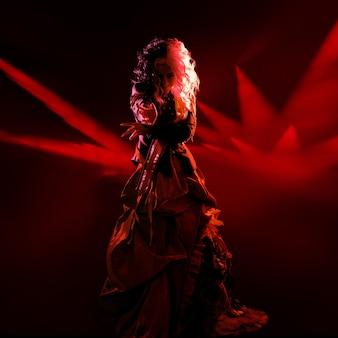 Звезда шоу, модная героиня на подиуме в красном свете.