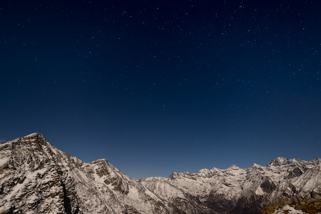 Звездное небо над альпами зимой при лунном свете