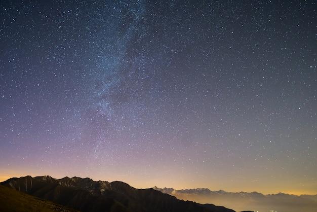 Звездное небо на рождество и величественный высокогорный массив итальянских французских альп