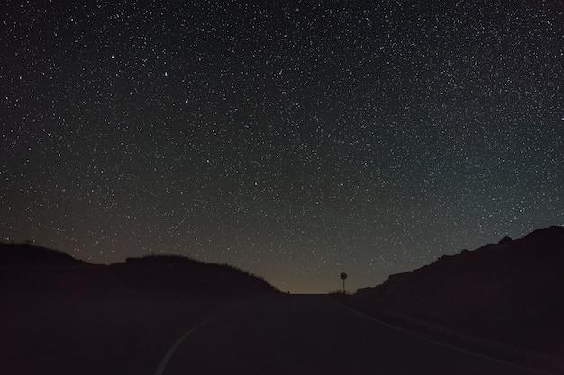 Звезды созвездия большой медведицы на ясном ночном небе над дорогой