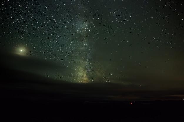 Звезды млечного пути ночью на небе светятся сквозь облака. вид на космическое пространство в пасмурную погоду.