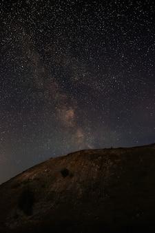 언덕이 많은 풍경 위에 밤하늘의 은하수 별