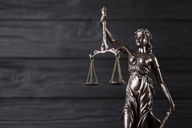정의의 여신상-정의의 여신 또는 정의의 로마 여신 justitia. 검은 나무 벽에 동상입니다. 사법 재판, 법정 절차 및 변호사 직업의 개념