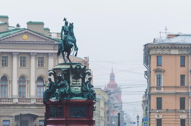 Статуя николая 1 в санкт-петербурге и вид на туманный город.