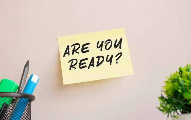 스티커는 사무실 벽에 붙어 있습니다. 스티커에 주의사항이 있습니다. are you ready 텍스트는 손으로 쓴 것입니다.