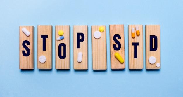 Stop std написано на деревянных блоках на голубом столе рядом с таблетками.