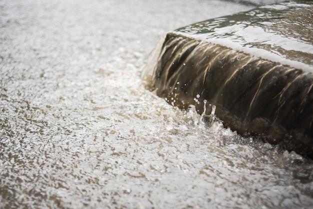 물의 흐름이 보도에서 아래로 흐릅니다. 폭우. 빗속의 거리 풍경. 비오는 가을 날씨.