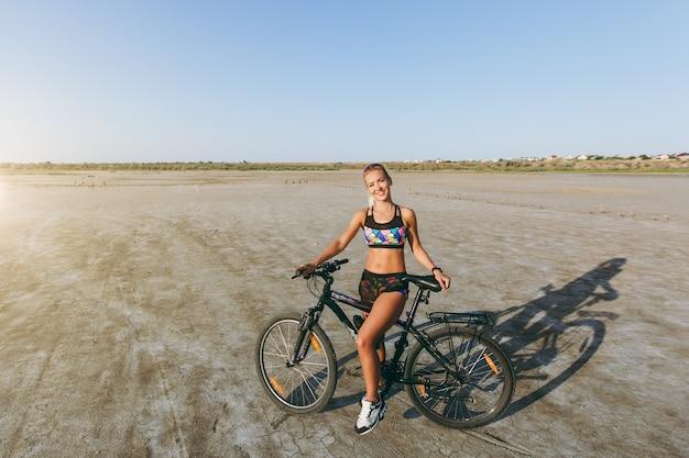 カラフルなスーツを着た強い金髪の女性が砂漠地帯の自転車の近くに立っています。フィットネスのコンセプト。