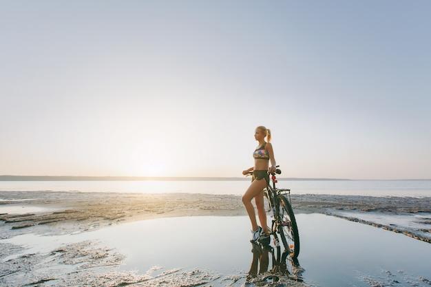 カラフルなスーツを着た強い金髪の女性が、水の近くの砂漠地帯で自転車の近くに立っています。フィットネスのコンセプト。