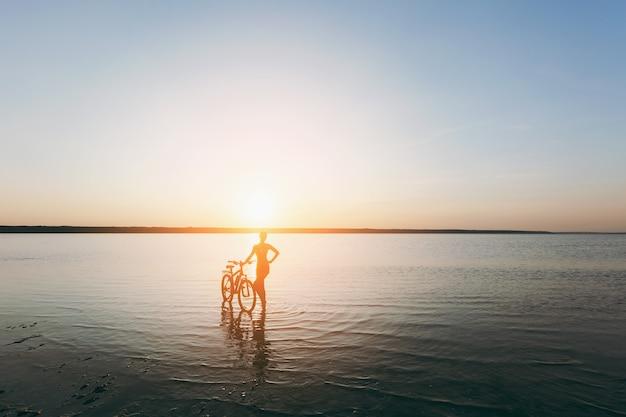Сильная блондинка в ярком костюме стоит возле велосипеда в воде на закате в теплый летний день. концепция фитнеса.