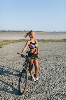 色とりどりのスーツを着た強い金髪の女性が砂漠地帯の自転車の近くに立って太陽を見ています。フィットネスのコンセプト。