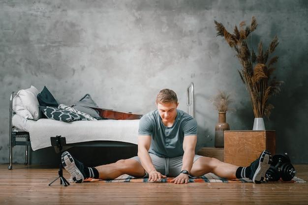 강한 남자는 집에서 스포츠를하러 간다. 금발 머리를 가진 쾌활한 스포티 한 남자가 다리에 뻗어 침실에서 블로그를 촬영합니다.