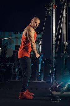 強い筋肉質の男がジムでトレーニング