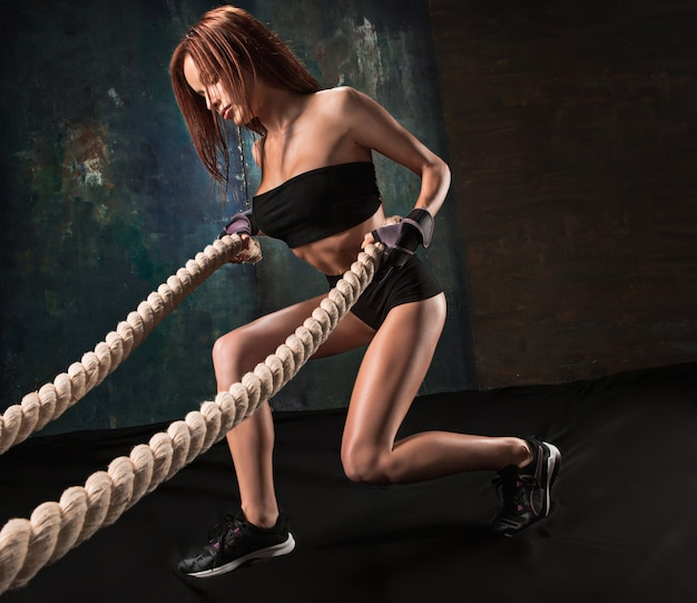 Сильная молодая женщина, потянув веревку в тренажерном зале