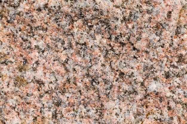 くぼみと不均一な構造、クローズアップテクスチャ背景を持つ現在の壊れた石の構造