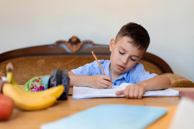 生徒は宿題をし、大きなノートに注意深く書き、家で大きな木製のテーブルで働き、空腹の場合に備えてノートの横にバナナを置きます。