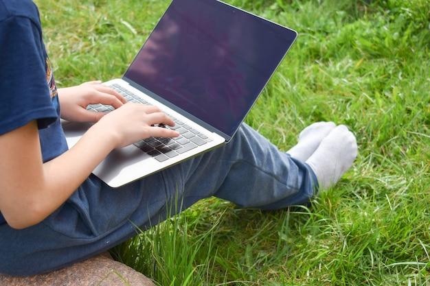 生徒は庭でコンピューターを使って学習します。