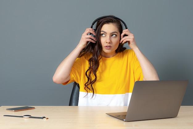 学生はヘッドセットを持ってコンピューターに座って、オンラインでビデオチュートリアルを見たり聞いたりします。