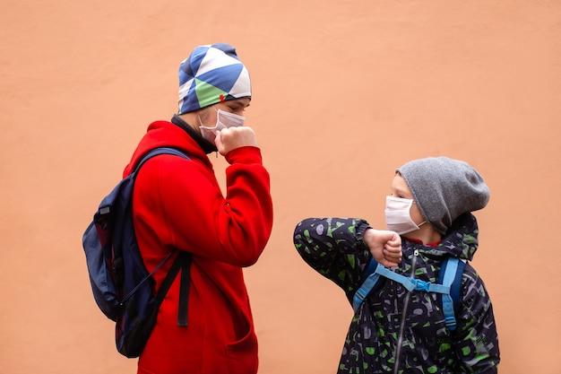 Студенты в защитных масках приветствуют друг друга локтями