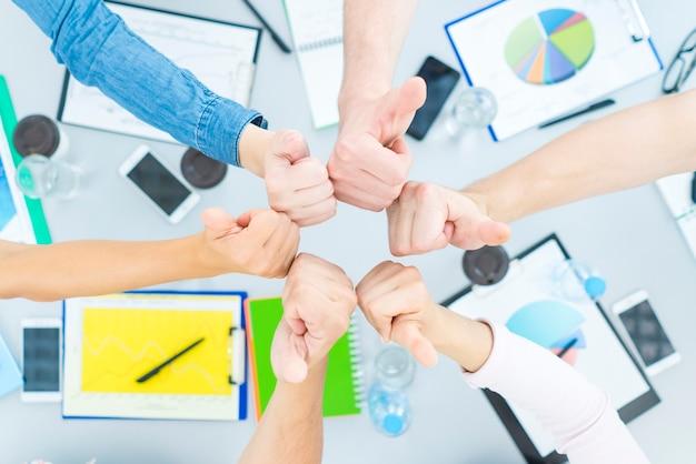 Студенты показывают пальцем на стол. вид сверху