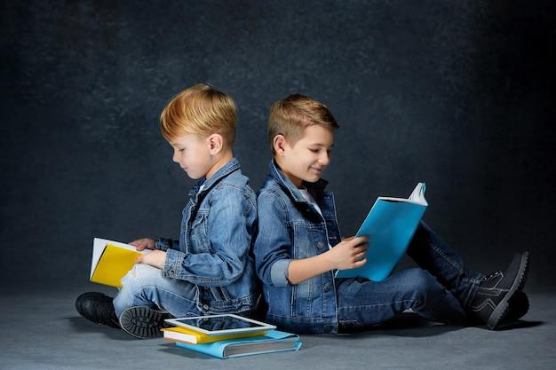 책과 태블릿을 가진 아이들의 스튜디오 샷