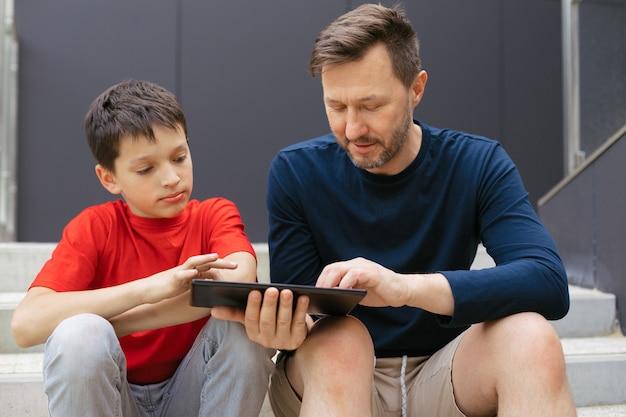 現代の家族の都市生活のスタイル。お父さんと息子はコンクリートの階段の階段でタブレットを使用しています。現代の技術コンセプト