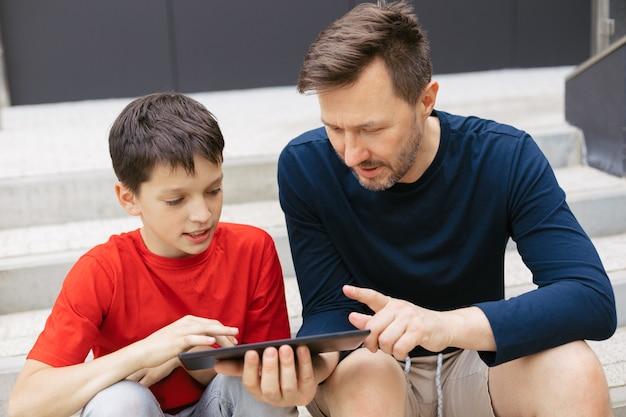 現代の家族の都市生活のスタイル。お父さんと息子はタブレットを使ってオンラインで遊ぶ