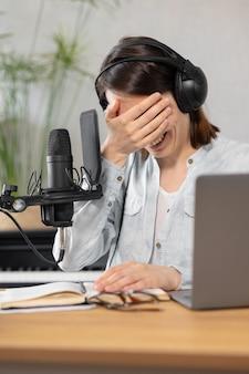 スタイリッシュで教育を受けた白人女性は、レコーディングスタジオまたは自宅でポッドキャストを録音します。