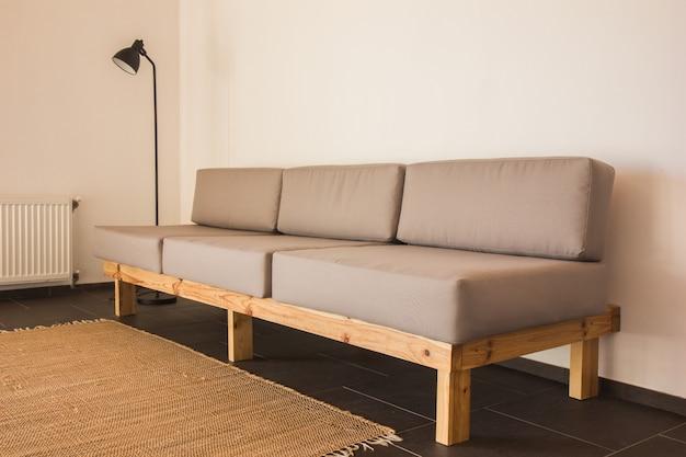 リビングルームのインテリアにスタイリッシュな自由奔放に生きるコンポジション。デザイングレーのソファー、木製のコーヒーテーブル、トイレ、エレガントなパーソナルアクセサリー。はちみつ黄色の枕とチェック柄。居心地の良いアパート。室内装飾