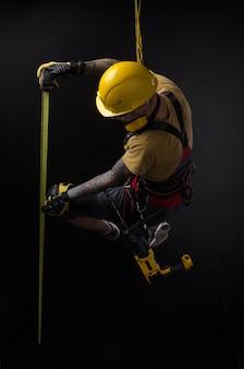 스타일리시한 등반가 빌더는 도구를 손으로 잡고 작업합니다. 검은 배경. 과거를 복사하다