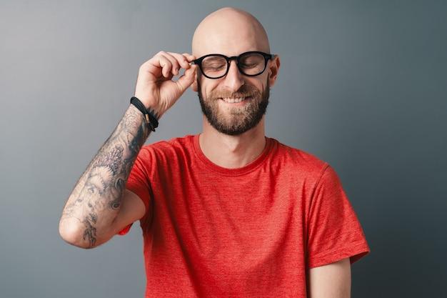 웃고있는 동안 문신을 한 손으로 그의 검은 색 액자 안경을 고정하는 세련된 젊은 수염 난 남자