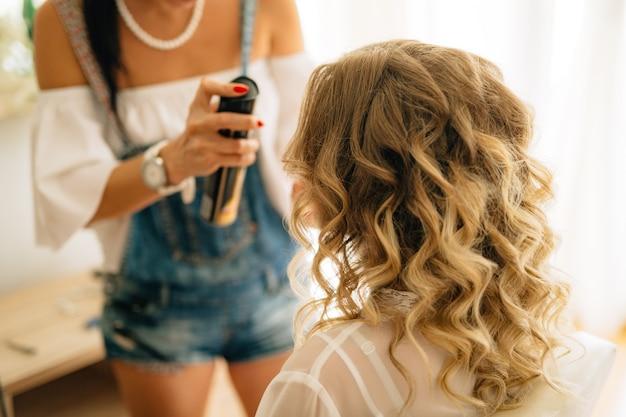 Стилист закрепляет укладку для женщины с длинными светлыми волосами с помощью лака для волос.