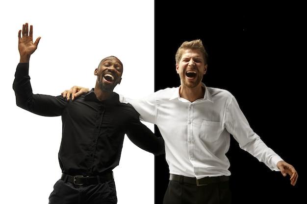 成功幸せなアフロと白人男性。混血のカップル。白と黒のスタジオで男性モデルのダイナミックな画像。人間の顔の感情の概念。