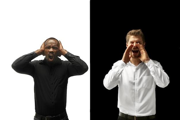 成功幸せなアフロと白人男性。混血のカップル。白と黒のスタジオでの男性モデルのダイナミックな画像。人間の顔の感情の概念。
