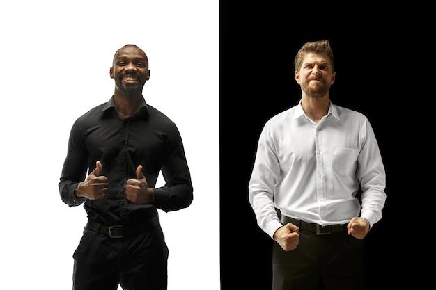 Успеху порадовали афро-кавказские мужчины. смешанная пара. динамическое изображение мужских моделей на черно-белой студии. концепция человеческих лицевых эмоций.