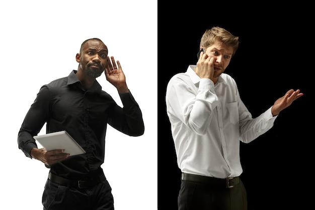 Успеху порадовали афро- и кавказские мужчины. смешанная пара с гаджетом. динамическое изображение мужских моделей на черно-белой студии. концепция человеческих лицевых эмоций.