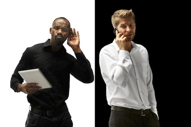 Успеху порадовали афро-кавказские мужчины. смешанная пара с гаджетом. динамическое изображение мужских моделей на черно-белой студии. концепция человеческих лицевых эмоций.